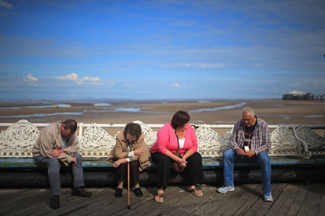 BLACKPOOL, ENGLAND - AUGUST 15: Holidaymakers sit on the pier and soak up the sunshine in Blackpool where visitor numbers have been the highest in decades, according to the #Blackpoolsback campaign on August 15, 2014 in Blackpool, England. A giant beach ball measuring a height of 16.6 meters was earlier inflated beating the previous world record of 15.8 meters to mark the #Blackpoolsback campaign. (Photo by Christopher Furlong/Getty Images)