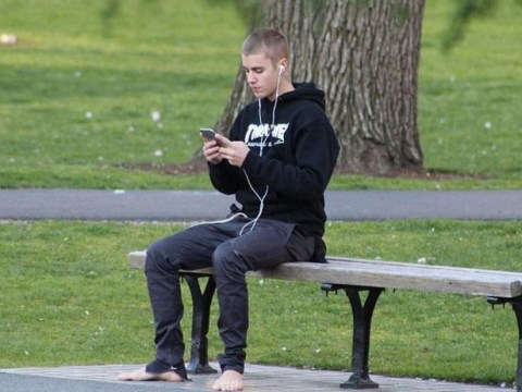 Justin Bieber walks through a park without any shoes, stops to feed squirrels