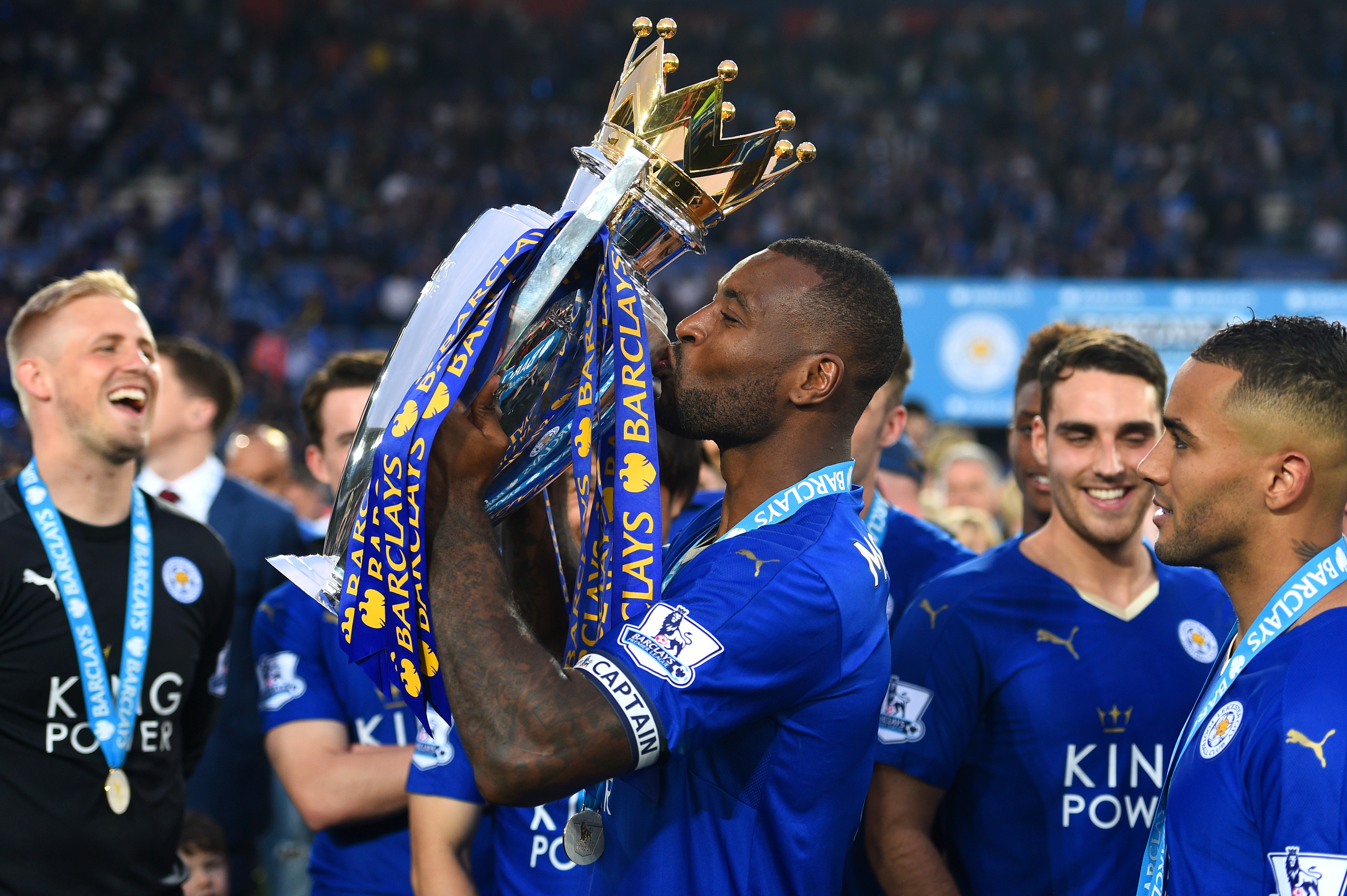 LEICESTER, ENGLAND - MAY 07: Wes Morgan of Leicester City kisses the Premier League Trophy as players and staffs celebrate the season champions after the Barclays Premier League match between Leicester City and Everton at The King Power Stadium on May 7, 2016 in Leicester, United Kingdom. (Photo by Shaun Botterill/Getty Images)