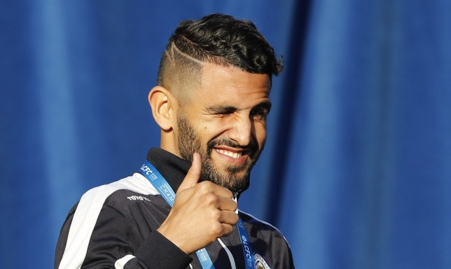 Leicester City's Algerian midfielder Riyad Mahrez gestures to fans as he arrives on stage to pase with teammates and the Premier league trophy as the Leicester City football team celebrate in Victoria Park, after taking part in an open-top bus parade through Leicester, to celebrate winning the Premier League title on May 16, 2016. / AFP / ADRIAN DENNIS (Photo credit should read ADRIAN DENNIS/AFP/Getty Images)