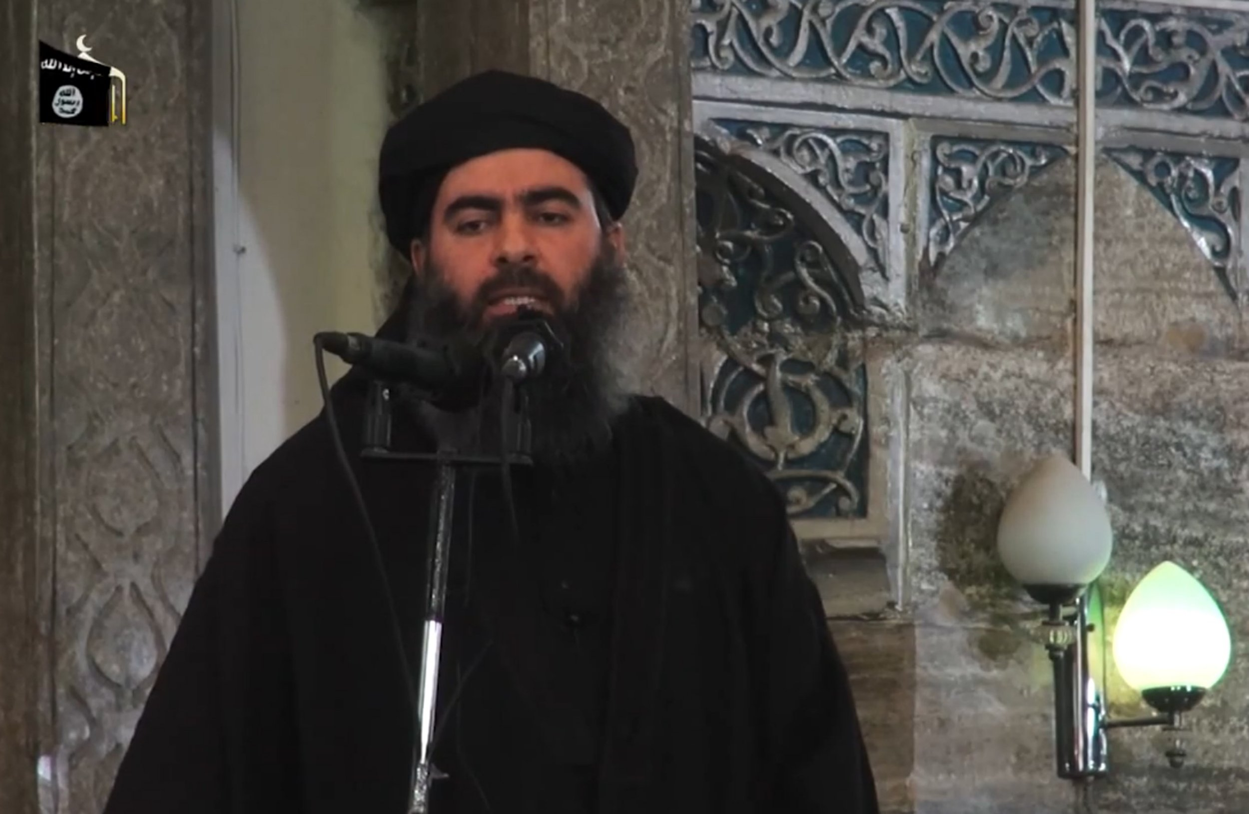 """Leader of the Islamic State (IS) jihadist group, Abu Bakr al-Baghdadi, adressing Muslim worshippers at a mosque in the militant-held northern Iraqi city of Mosul. Iraq claimed on October 11, 2015 to have struck a convoy carrying Islamic State group leader Abu Bakr al-Baghdadi in an air raid near the Syrian border but said his fate was unknown. (FILES) An image grab taken from a propaganda video released on July 5, 2014 by al-Furqan Media. AFP PHOTO / HO / AL-FURQAN MEDIA == RESTRICTED TO EDITORIAL USE - MANDATORY CREDIT """"AFP PHOTO / HO / AL-FURQAN MEDIA """" - NO MARKETING NO ADVERTISING CAMPAIGNS - DISTRIBUTED AS A SERVICE TO CLIENTS FROM ALTERNATIVE SOURCES, AFP IS NOT RESPONSIBLE FOR ANY DIGITAL ALTERATIONS TO THE PICTURE'S EDITORIAL CONTENT, DATE AND LOCATION WHICH CANNOT BE INDEPENDENTLY VERIFIED ==-/AFP/Getty Images"""
