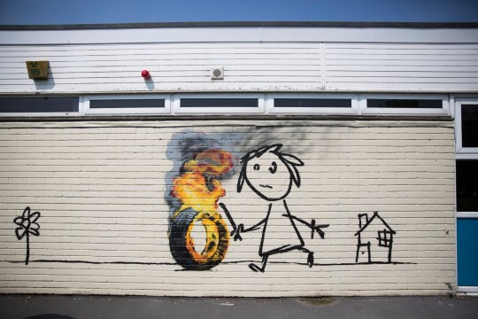 Banksy paints Bridge Farm Primary Bristol wall as 'present' Credit: SWNS. GV of the new Banksy mural at the Bridge Farm Primary School in Bristol. June 6 2016. See SWNS story SWBANKSY: Pupils and teachers returned to their school after half-term to find a genuine BANKSY on the wall of classroom. The famous artist spray painted a stick-wielding child chasing a burning tyre on the side of Bridge Farm Primary School. It is believed the work is a modern take on hoop rolling, a popular game played by children during the Victorian days. The six-foot high artwork also features a flower and a small house with 'Banksy' signed to the bottom left of the brick building.
