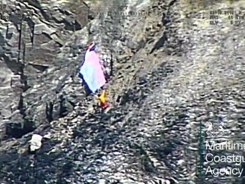 Paraglider trapped after winds blow him on to cliff face