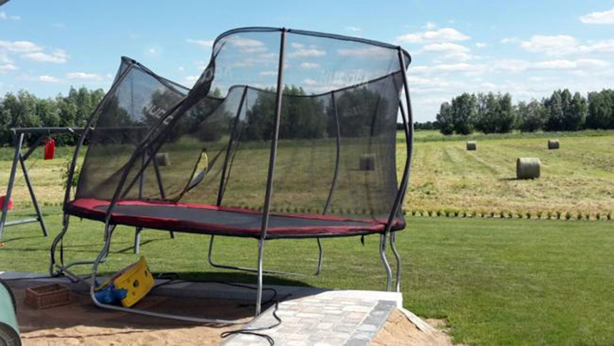 Pic shows: the tromboline. A five-year-old girl incredibly survived being thrown onto the roof of a house in a trampoline after it was ripped off the ground and tossed into the air by a tornado. The girl had been playing on the trampoline that was surrounded by a safety net with two other children in Banzkow, a municipality in Mecklenburg-Vorpommern, in northern Germany. But according to emergency services a tornado had then suddenly swept through the garden, ripping the trampoline from its attachments. The grandmother of the children rushed to pull two of them from the apparatus but was unable to rescue the five-year-old, who was swept up on to the roof by the wind along with the trampoline. The trampoline crashed to the floor again but the child stayed on the roof and managed to escape the near-disaster with only a few cuts and bruises. Her grandfather was then able to rescue her with a ladder. Nearby, firemen said that the wind also managed to toss a paddling pool in the air before dumping it some 800 metres (2,624 feet) away. (ends)