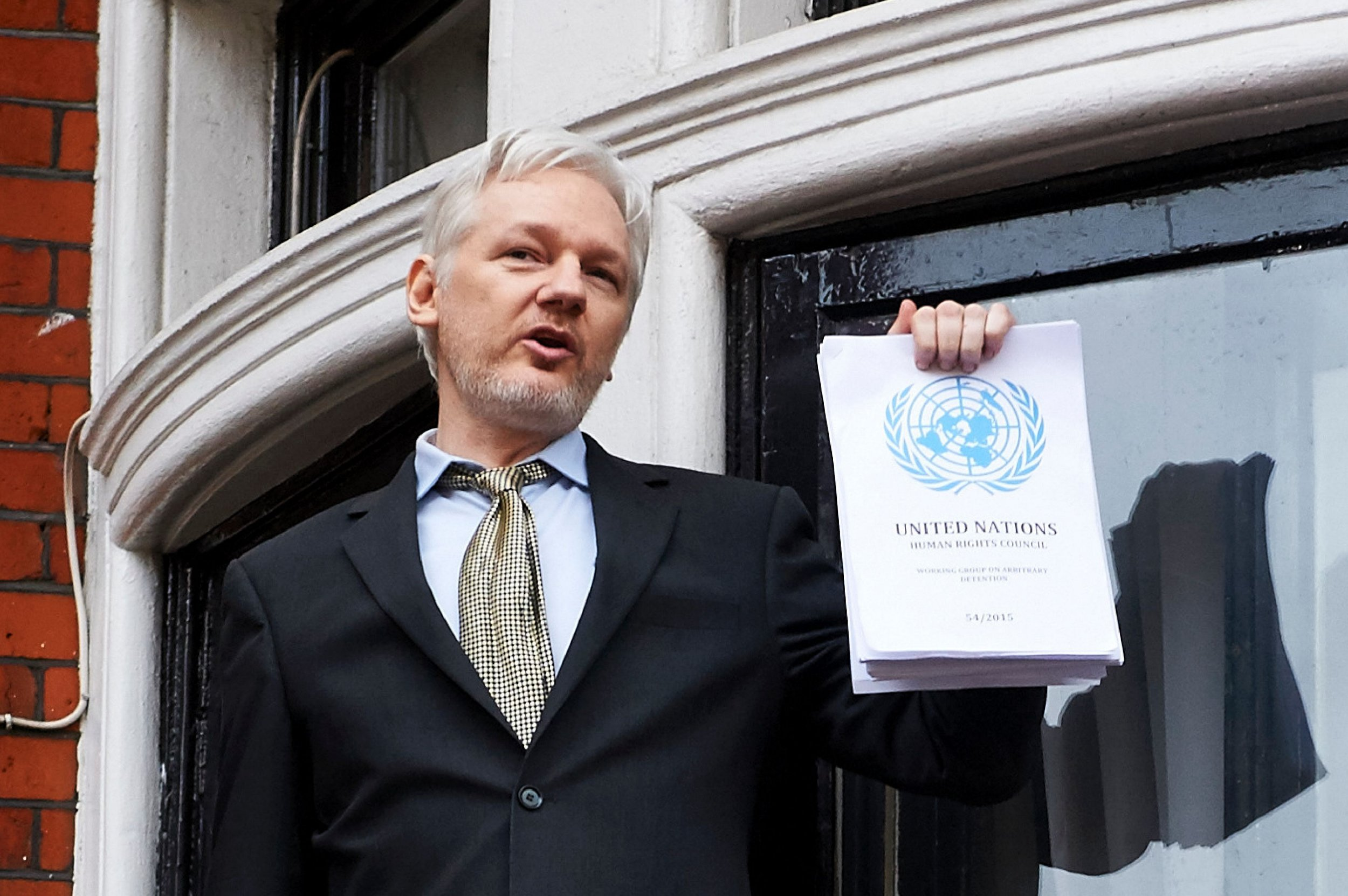 """WikiLeaks founder Julian Assange addresses the media holding a printed report of the judgement of the UN's Working Group on Arbitrary Detention on his case from the balcony of the Ecuadorian embassy in central London on February 5, 2016.nDuring a press conference on February 5 Julian Assange, speaking via video-link, called for Britain and Sweden to """"implement"""" a UN panel finding saying that he should be able to walk free from Ecuador's embassy, where he has lived in self-imposed confinement since 2012. / AFP / NIKLAS HALLE'N        (Photo credit should read NIKLAS HALLE'N/AFP/Getty Images)"""