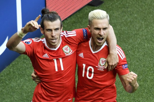 Wales' forward Gareth Bale (L) and Wales' midfielder Aaron Ramsey celebrate after an own goal by Northern Ireland's defender Gareth McAuley (not pictured) during the Euro 2016 round of sixteen football match Wales vs Northern Ireland, on June 25, 2016 at the Parc des Princes stadium in Paris. / AFP / PHILIPPE LOPEZ (Photo credit should read PHILIPPE LOPEZ/AFP/Getty Images)