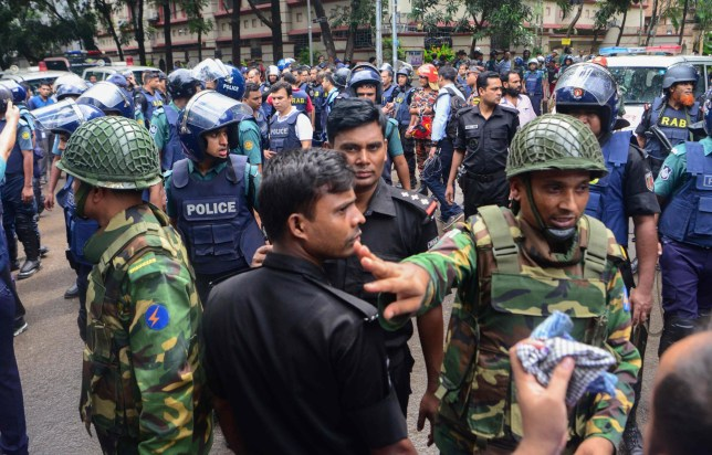 Bangladeshi police and military gather in an intersection near an upscale restaurant after a bloody siege ended in Dhaka on July 2, 2016. Heavily armed militants murdered 20 hostages in Bangladesh, hacking many of their victims to death, before six of the attackers were gunned down at the end of a siege July 2 at a restaurant packed with foreigners. As the Islamic State (IS) group claimed responsibility for the carnage at the start of the Eid holiday, Prime Minister Sheikh Hasina said she was determined to eradicate militancy in the mainly Muslim nation. / AFP PHOTO / STRSTR/AFP/Getty Images