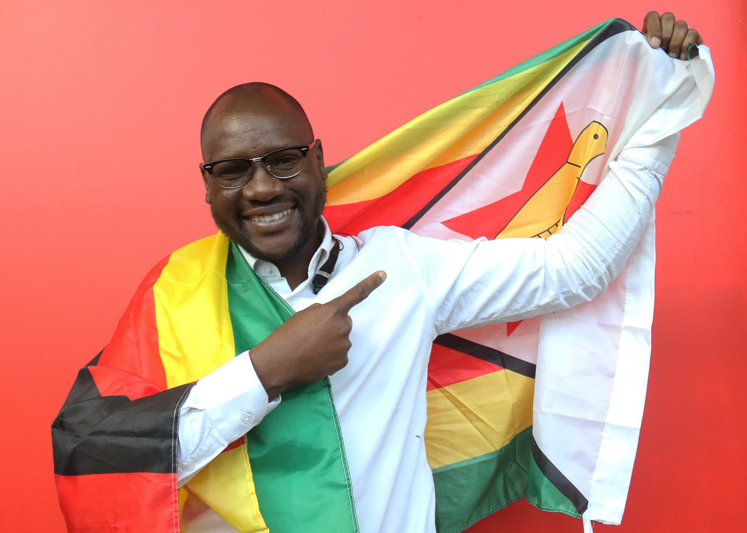 FILE - In this Tuesday May 3, 2016 file photo, shows Evans Mawarire, a young pastor, posing with a Zimbabwean flag in Harare, Zimbabwe. Zimbabwe police have charged Mawarire on Tuesday July 12, 2016, with inciting violence and disturbing the peace. (AP Photo/Tsvangirayi Mukwazhi, File)