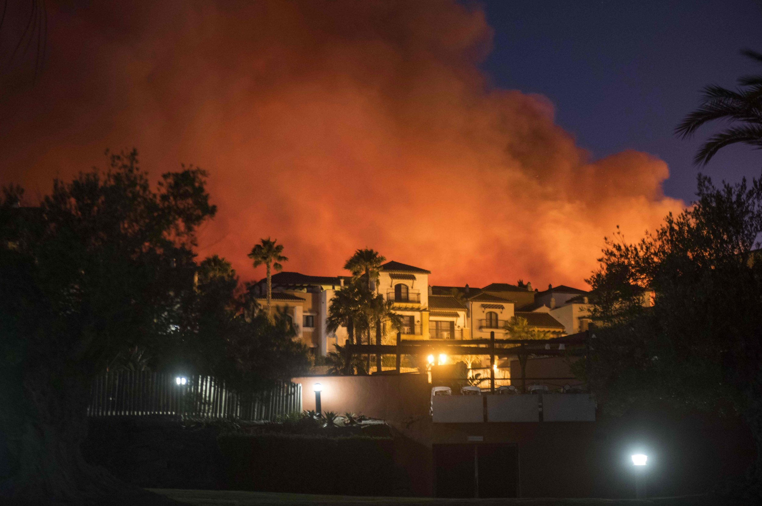 TOPSHOT - A wildfire threatens Hotel Aldiana in the seaside resort of Alcaidesa, near Sotogrande, province of Cadiz Spain, on July 12, 2016. About 420 guests staying at the hotel, mostly German and British, were forced to take shelter at a nearby sports complex. / AFP PHOTO / Marcos MorenoMARCOS MORENO/AFP/Getty Images