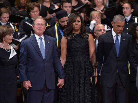Michelle Obama looks on awkwardly as George Bush dances during Dallas police memorial