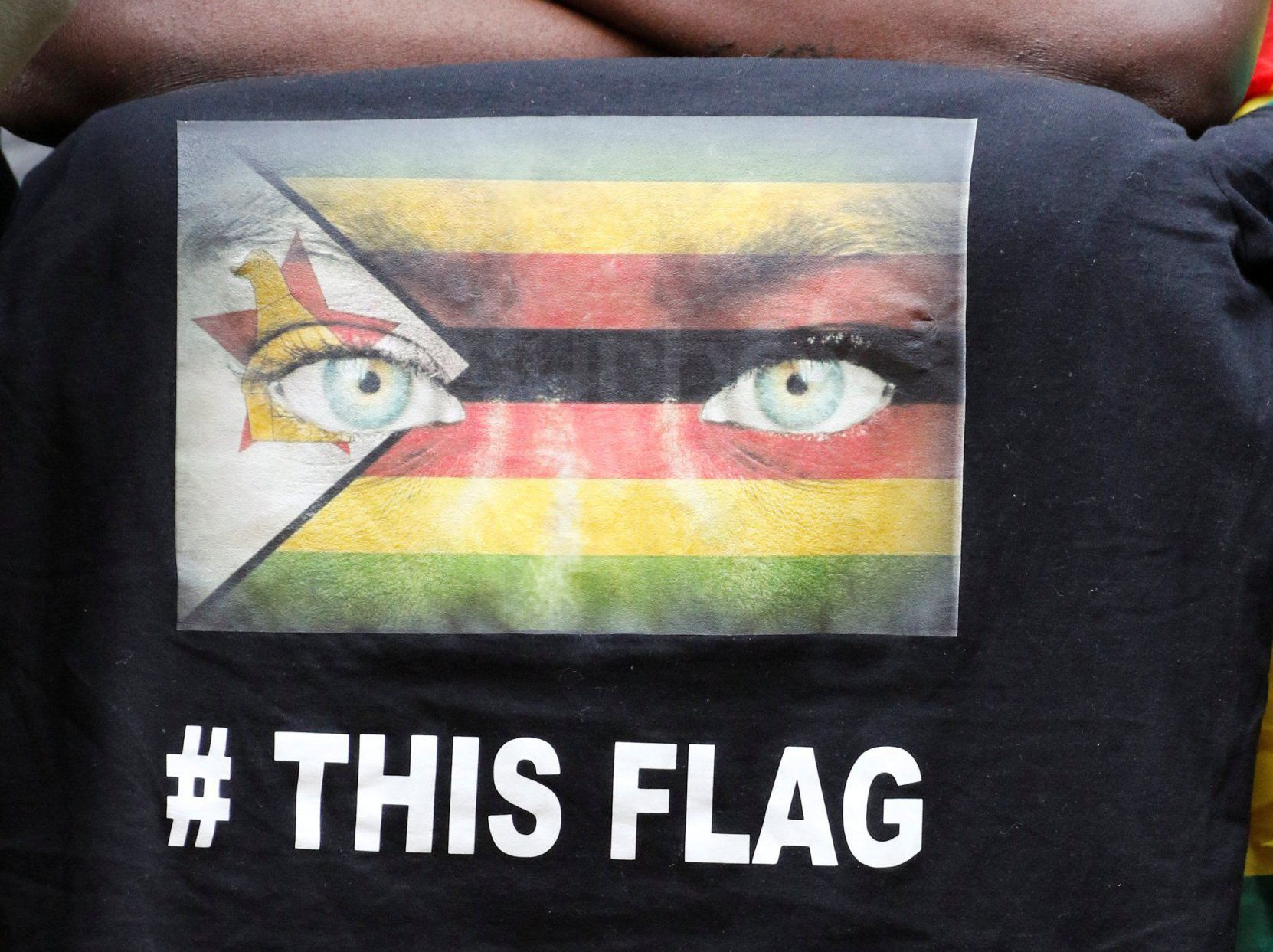 A supporter of Zimbabwean Pastor Evan Mawarire's displays t-shirt with a flag as he sits outside the Harare Magistrates court during Mawarire's trial, July 13, 2016. REUTERS/Philimon Bulawayo