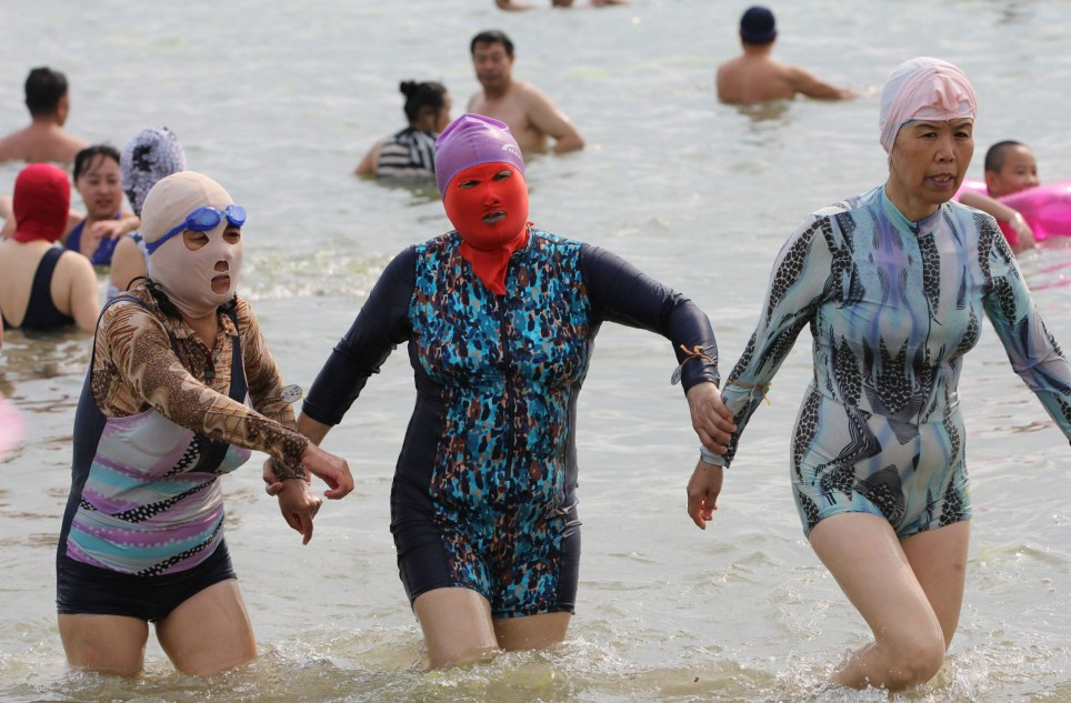 QINGDAO, CHINA - JULY 13: Visitors wear facekinis play in water on July 13, 2016 in Qingdao, Shandong Province of China. Facekini is originally designed from diving cap in 2004 in Qingdao City to protect face from sun damage and jellyfishes. (Photo by VCG/VCG via Getty Images)