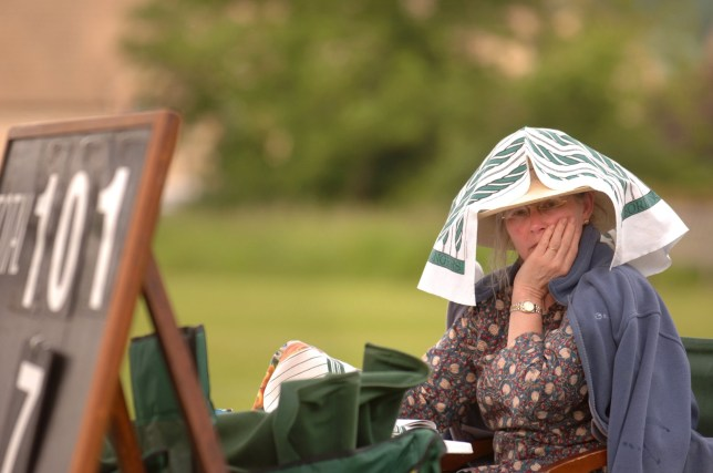 AXJ2M5 A SCORER AT A VILLAGE CRICKET MATCH WITH A TEA TOWEL ON HER HEAD GLOUCESTERSHIRE UK. Image shot 2006. Exact date unknown.