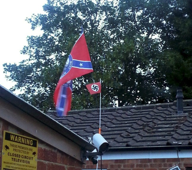 """A Nazi flag has been spotted flying high at a home in Cheltenham, Gloucestershire. See SWNS story SWNAZI; Neighbours were horrified to see the symbol of hate above a house alongside an American Confederate flag, which is associated with racist groups like the Ku Klux Klan. The swastika-emblazoned flag can be clearly seen by passers by. The picture was snapped in Cheltenham yesterday and a local, who preferred not to be named, said: """"This is likely to cause a lot of offence in the area. """"Why would you put up a Nazi flag in your garden? It's horrific and people will find it very unsettling."""""""