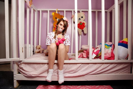 Jess pictured sitting in her cot at home (Picture: Barcroft)