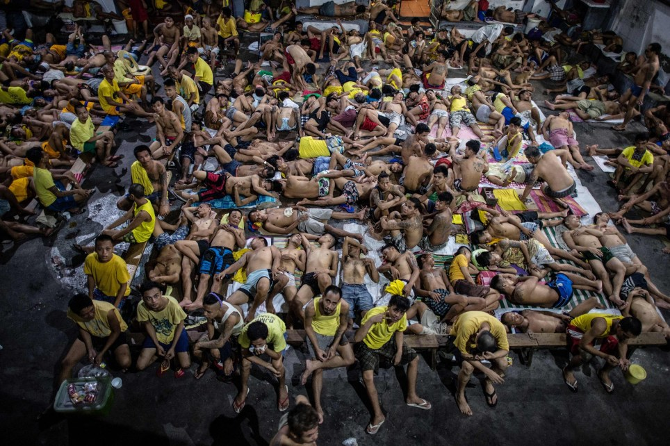 Inmates sleep on the ground of an open basketball court inside the Quezon City jail at night in Manila in this picture taken on July 21, 2016. There are 3,800 inmates at the jail, which was built six decades ago to house 800, and they engage in a relentless contest for space. Men take turns to sleep on the cracked cement floor of an open-air basketball court, the steps of staircases, underneath beds and hammocks made out of old blankets. / AFP PHOTO / NOEL CELIS / TO GO WITH AFP STORY: Philippines-politics-crime-jails, FOCUS by Ayee MacaraigNOEL CELIS/AFP/Getty Images
