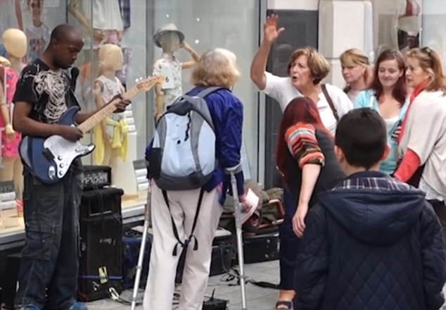 Crowds reacted angrily to the woman when she tried to silence the busker in Liverpool (Picture: Youtube/John Baxter Walker)
