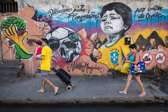 Carlos Dantas, thirty-six, and his family walk back to their soon-to be demolished home that is to make way for a car park; a painted mural on its outer wall depicts a young boy dressed in the Brazilian national football (soccer) team in the classic yellow jersey crying because of the eviction he and his family will face due to the proximity of his home to the Maracan? stadium as it completes its facelift for the 2014 FIFA World Cup. Rio de Janeiro.