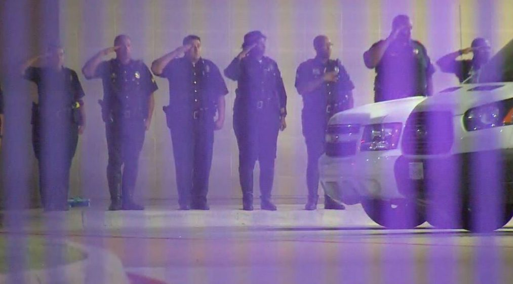Police officers show respect to the fallen outside Parkland Hospital early Friday morning. WFAA TV