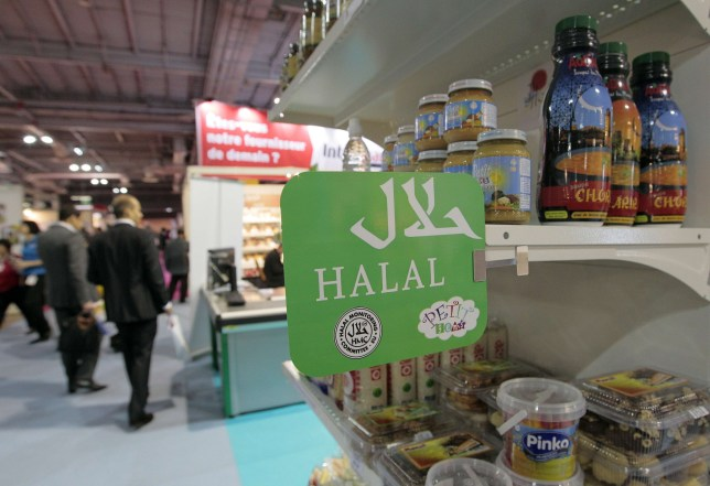 """People walk behind a stand of Halal food products on March 31, 2010 shown during the Halal expo, part of the """"Foods&goods"""" fair at the Porte de Versailles exhibition center in Paris. The expo, running until March 31, 2010, is a professional trade show for sellers and buyers, devoted entirely to halal foostuffs such as food and beverage, cosmetics, fashion, consumables. AFP PHOTO JACQUES DEMARTHON (Photo credit should read JACQUES DEMARTHON/AFP/Getty Images)"""