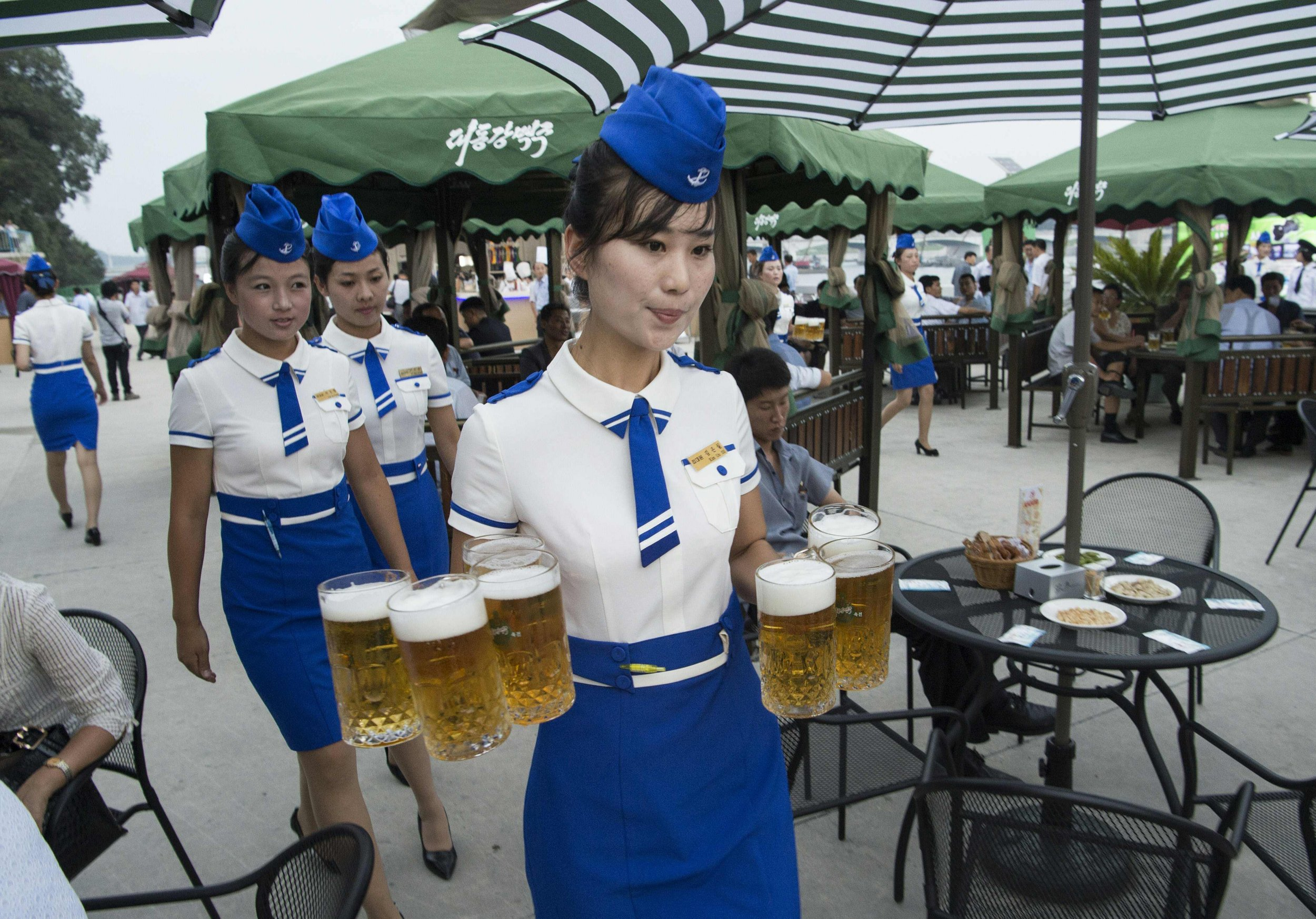 This photo taken on August 12, 2016 shows a waitress carrying jugs of beer to guests before the opening of the Pyongyang Taedonggang Beer Festival on the banks of the Taedong river in Pyongyang. / AFP PHOTO / Kim Won-JinKIM WON-JIN/AFP/Getty Images