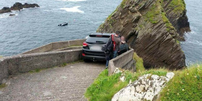Car stuck between a wall after the man drove down a footpath near Dunquin in the Republic of Ireland.. See SWNS copy SWSTUCK: This dopey driver was trapped in his car for 12 hours after he attempted to drive down a narrow pedestrian walkway - and got wedged. The motorist was trying to find somewhere to camp for the night when he headed down a steep walled track leading to a coastal ferry point. But his car got stuck between the low stone walls and he was unable to open the doors. He spent the night stranded in his car with a 200ft drop outside the window near Dunquin in the Republic of Ireland.