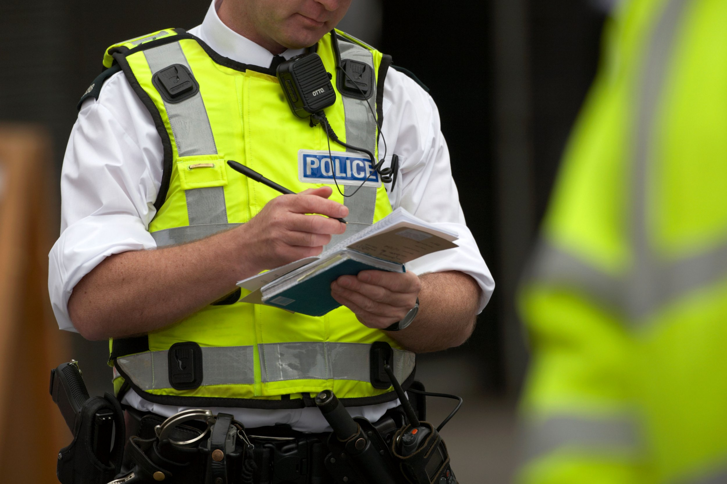 B0TMBA PSNI police service northern ireland officer in high vis jacket making notes in his notebook