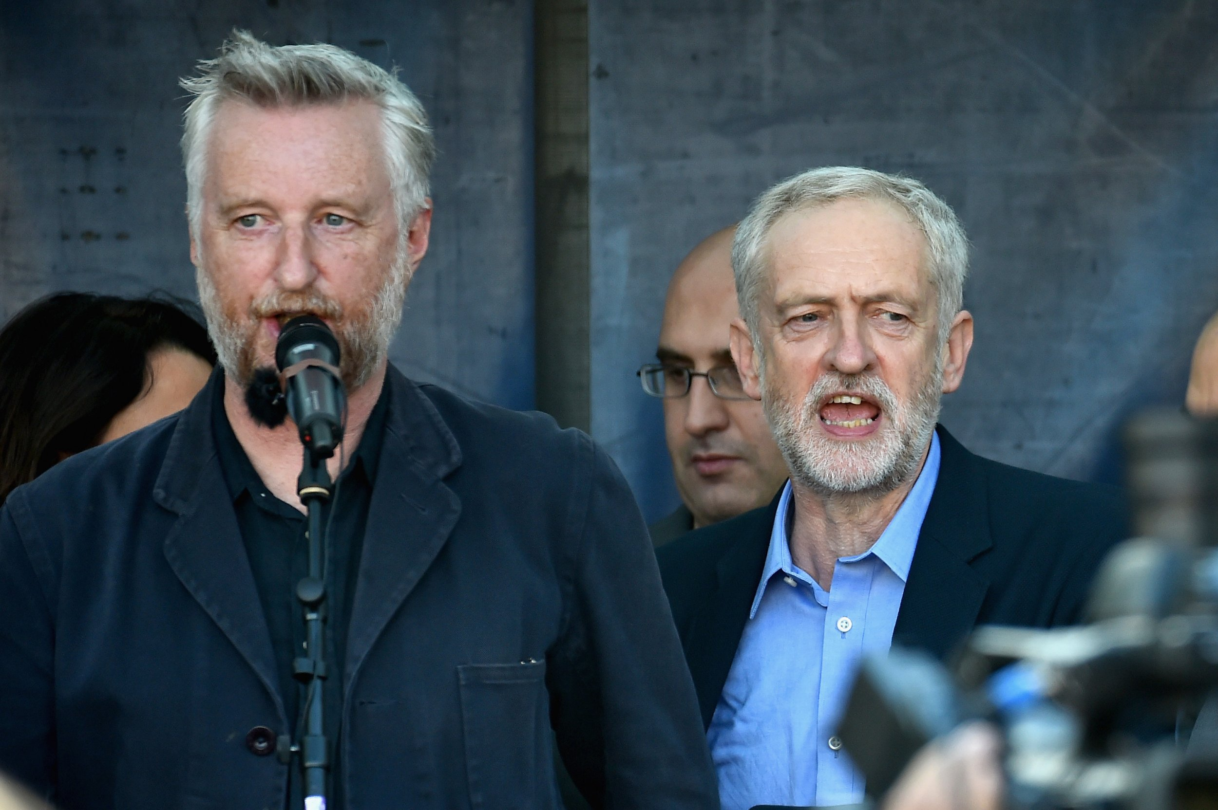 "LONDON, ENGLAND - SEPTEMBER 12: The new leader of the Labour Party Jeremy Corbyn (R) and singer songwriter Billy Bragg sing the ""The Red Flag"" at the Amnesty UK Front 'Solidarity With Refugees' demonstration on September 12, 2015 in London, England. The demonstrators are calling on David Cameron to accept more refugees already in Europe. Earlier in the week he announced the UK would take 20000 Syrians from refugee camps over four years. (Photo by Jeff J Mitchell/Getty Images)"