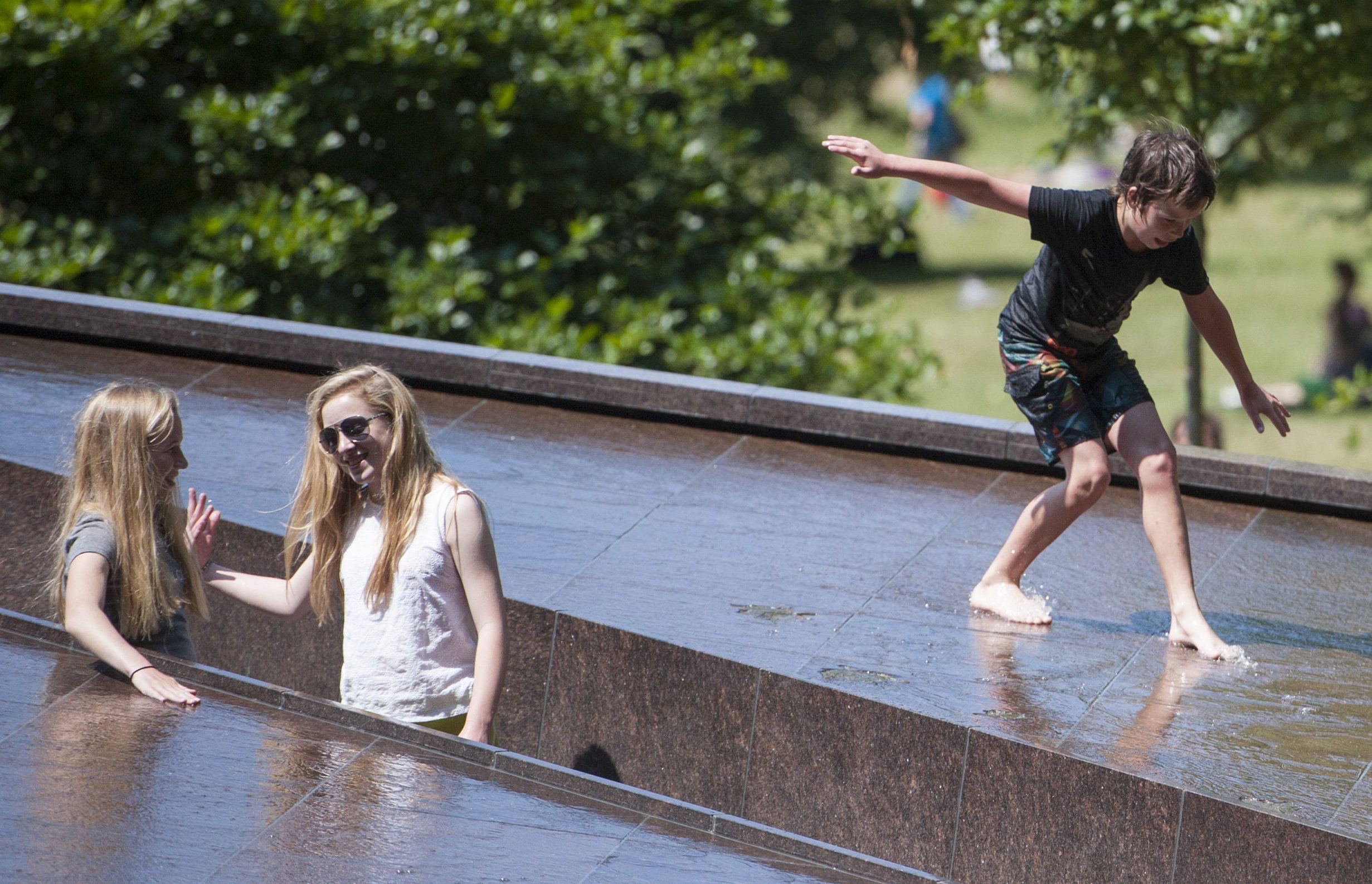 Mandatory Credit: Photo by Ray Tang/REX/Shutterstock (2627905e)nYoung boy sliding down Canada Memorial in St James ParknHot weather in London, Britain - 09 Jul 2013nn