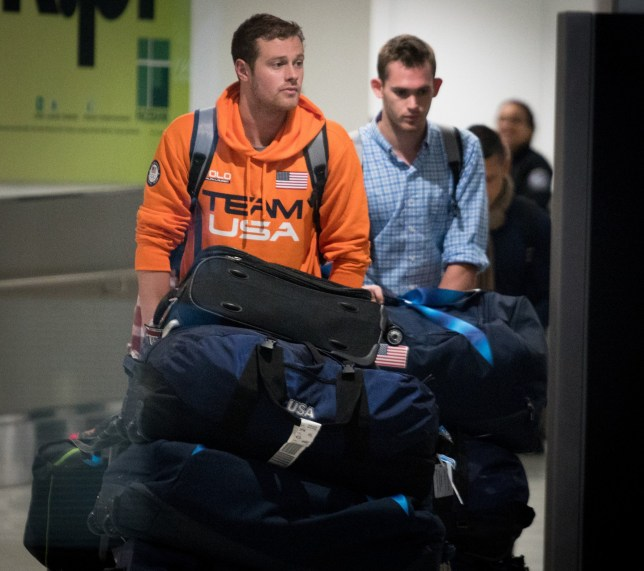 MIAMI, FL - AUGUST 19: USA National Swimming Team members Jack Conger (L) and Gunnar Bentz are escorted through the International terminal at Miami International Airport upon their arrival to the United States from Rio de Janeiro, Brazil on August 19, 2016 in Miami, Florida. Ryan Lochte, Gunnar Bentz, Jack Conger and Jimmy Feigen were involved in an altercation at a gas station in Rio on Sunday. Bentz and Conger were detained by Brazilian authorities while attempting to fly out of Brazil on August 17. Their claims of being victims of a late-night robbery are being questioned by police. (Photo by Angel Valentin/Getty Images)