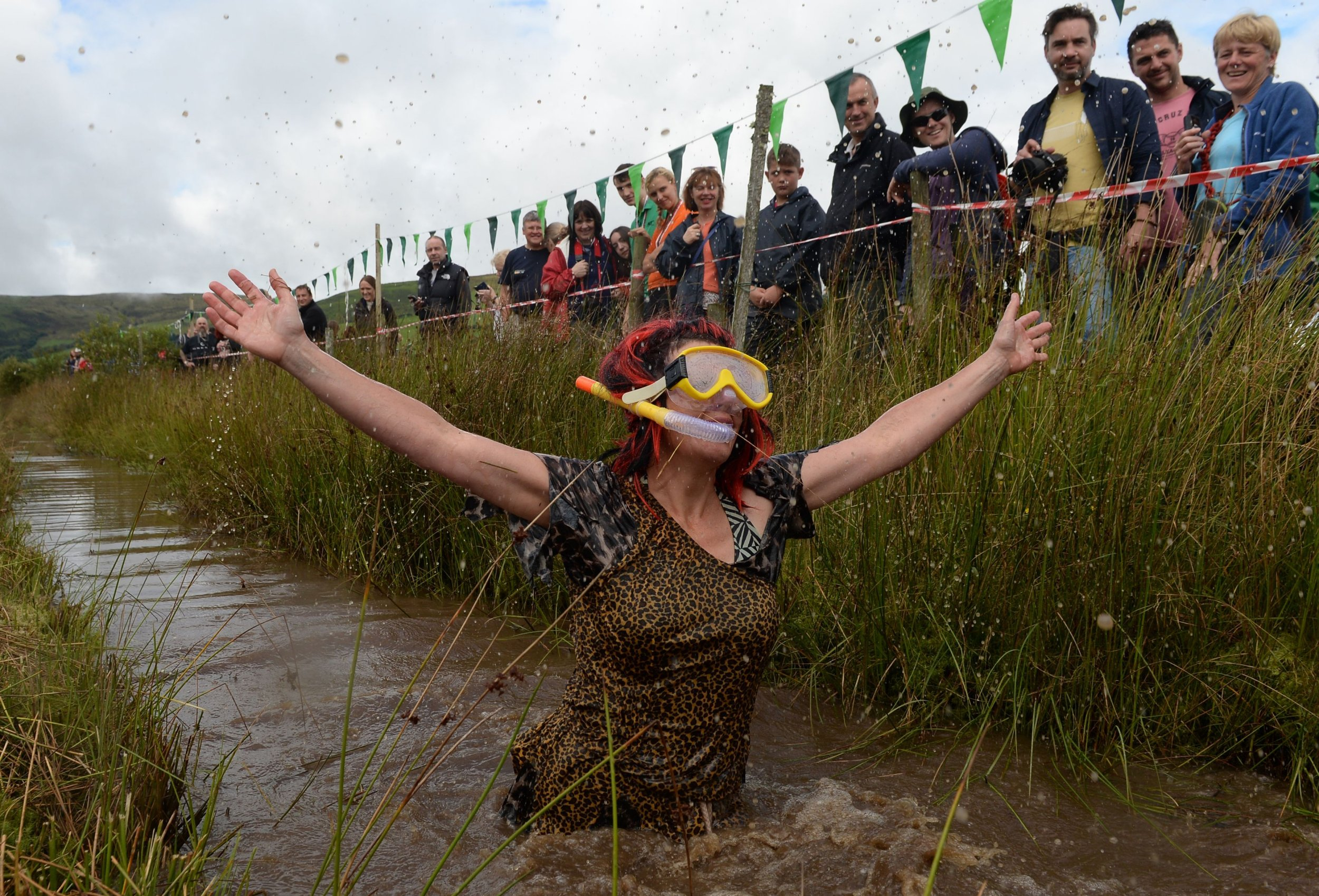 A competitor celebrates after taking part in the 31st World Bog Snorkelling Championships at Waen Rhydd peat bog in Llanwrtyd Wells, Wales. PRESS ASSOCIATION Photo. Picture date: Sunday August 28, 2016. Photo credit should read: Joe Giddens/PA Wire