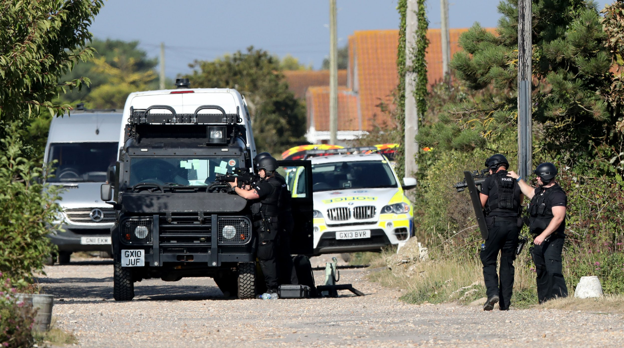 Armed police at the scene on Harbour Road, Pagham, West Sussex, where they are in a stand-off with a 72-year-old man who is thought to have a gun. PRESS ASSOCIATION Photo. Picture date: Monday August 29, 2016. Sussex Police, who have cordoned off the property and closed the road, said negotiators are continuing to make contact with the man. Emergency services are on stand-by. See PA story POLICE Pagham. Photo credit should read: Andrew Matthews/PA Wire