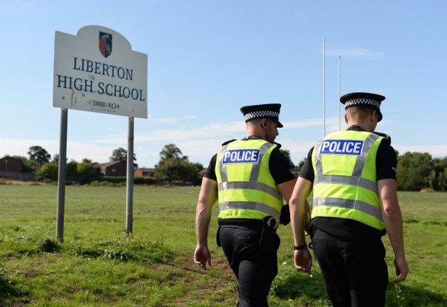Police at Liberton High School Edinburgh, Scotland, where the body of man has been found. August 30, 2016.   See Centre Press story CPBODY; A police investigation has been launched after a man's body was found at an Edinburgh school. The body was discovered in a wooded area at Liberton High School yesterday (Tues). Police say they are treating the death as unexplained. Edinburgh City Council said the school day was continuing as normal, and the body had been found at the bottom of the school playing fields. The school, in the south of the city, has been the location of a number of tragedies and incidents over recent years. In 2014, a 12-year-old pupil died at Liberton after a wall collapsed on top of her. Keane Wallis-Bennett was hit by the wall while getting changed in the girls' changing rooms and later died at the scene.