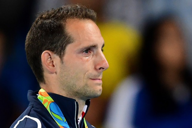 TOPSHOT - Silver medallist France's Renaud Lavillenie cries on the podium during the medal ceremony for the men's pole vault during the athletics event at the Rio 2016 Olympic Games at the Olympic Stadium in Rio de Janeiro on August 16, 2016. / AFP / FRANCK FIFE (Photo credit should read FRANCK FIFE/AFP/Getty Images)