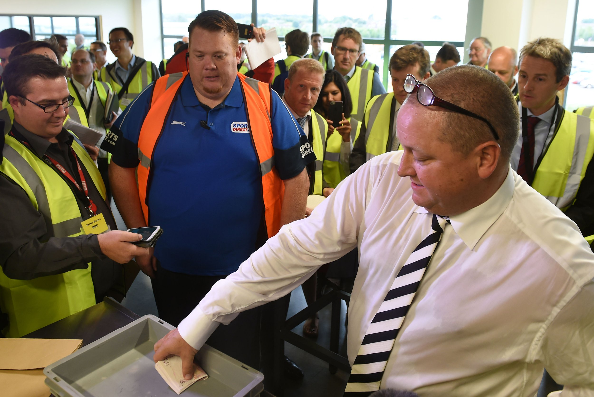 Sports Direct founder Mike Ashley empties his pockets of bank notes during a mock search at the Sports Direct headquarters in Shirebrook, Derbyshire. PRESS ASSOCIATION Photo. Picture date: Wednesday September 7, 2016. See PA story CITY SportsDirect. Photo credit should read: Joe Giddens/PA Wire