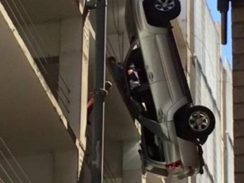 Driver suspended in mid-air after ploughing through car park barrier