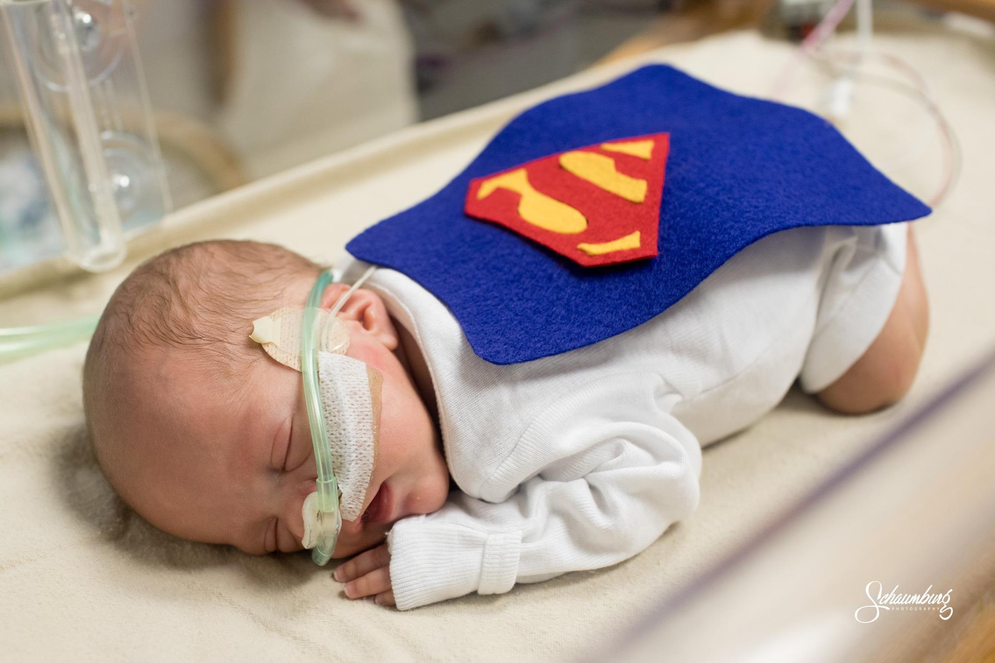 Nurse dress babies in superhero costumes