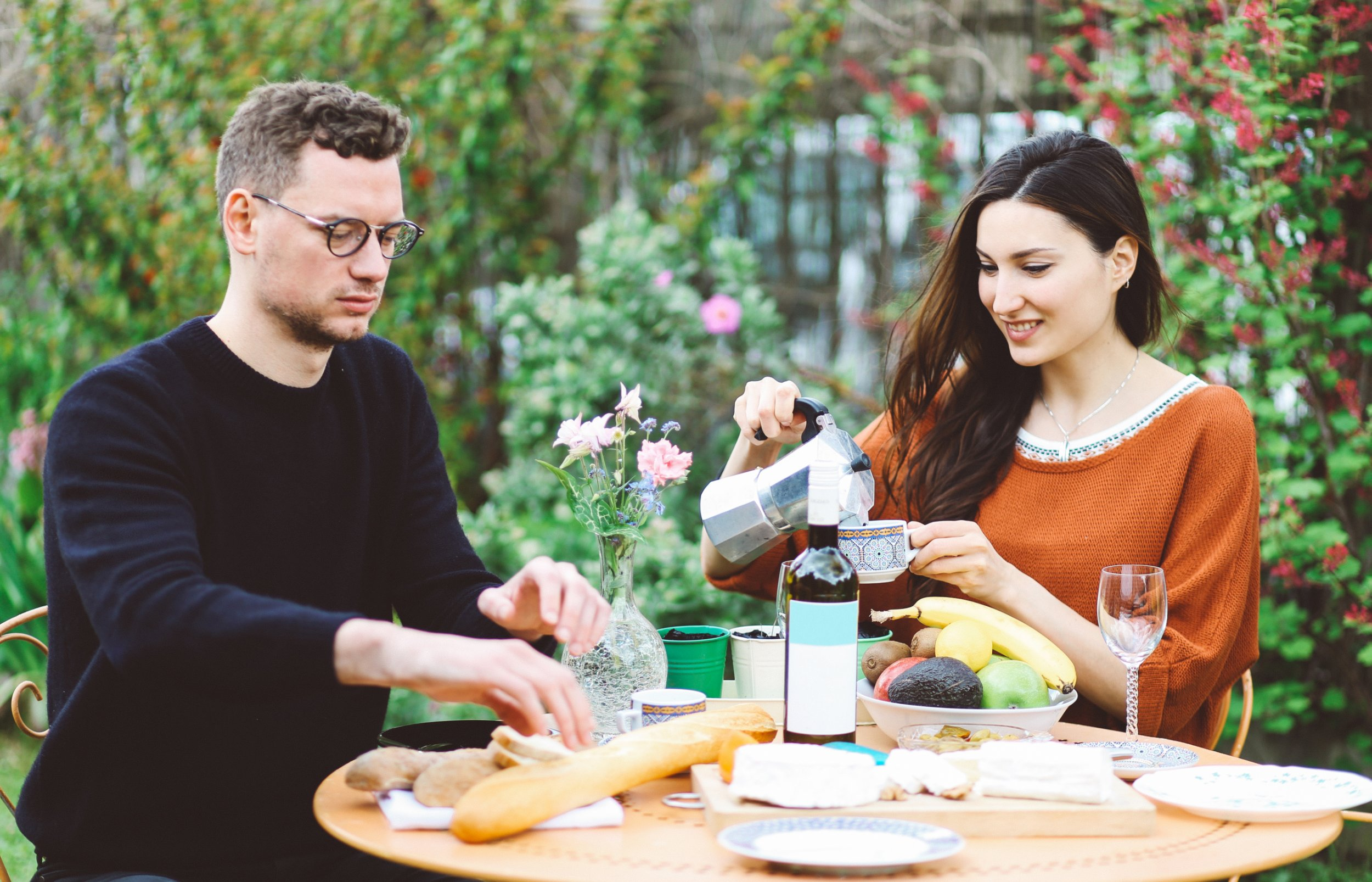 Vintage toned image of young couple having a lunch in the garden of a Paris suburban home, filled with traditional French food, different types of cheese, wine, home made baguette bread, coffee, and fruits and vegetables. They are enjoying the nice springtime weather, having a typical French brunch.