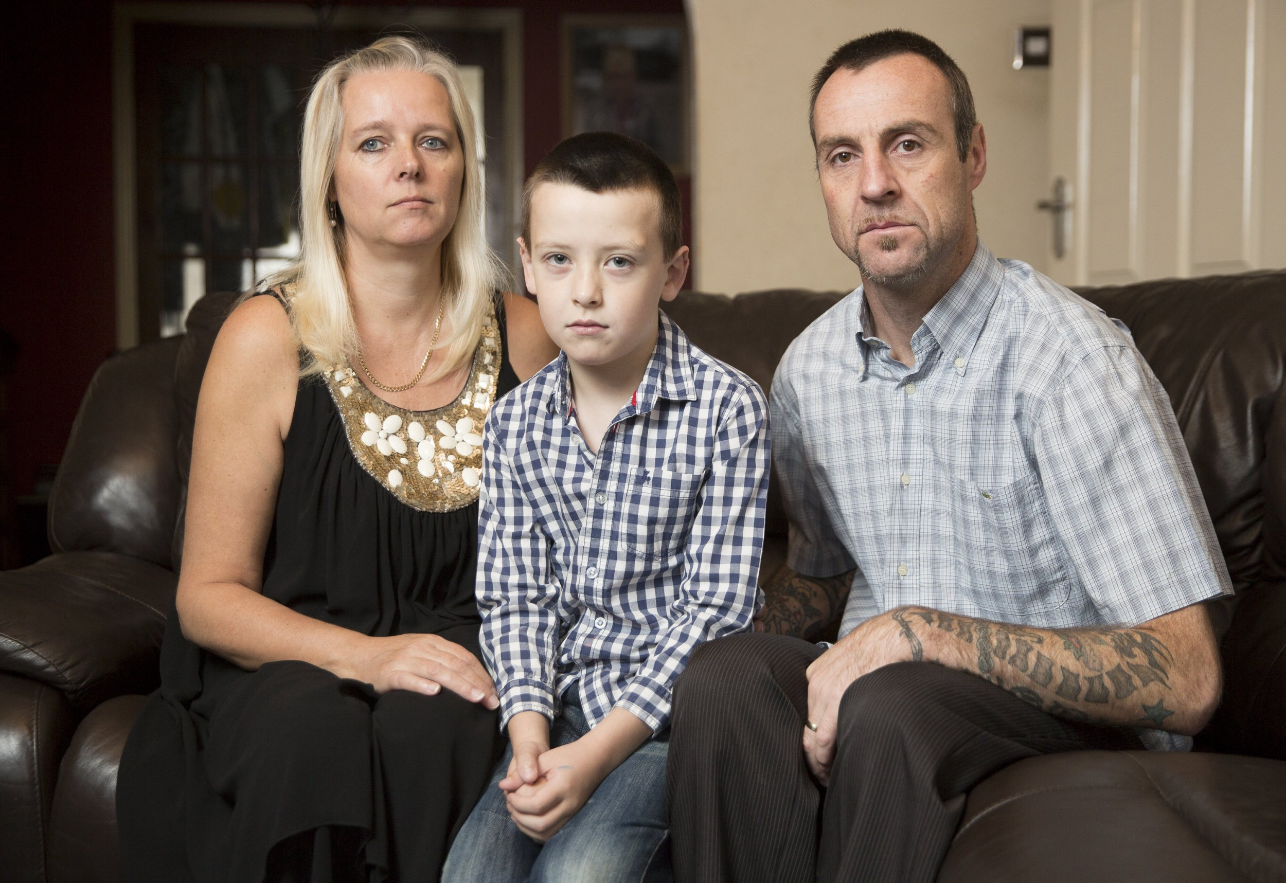 "Ben Gamble, eight, with his parents Paul and Jackie, from Coventry. Ben, who was born with half a heart, has had his disability benefits taken away. See NTI story NTIHEART: A schoolboy born with half a heart had his benefits taken away by the Government - on his eighth BIRTHDAY. Brave Ben Gamble has undergone five operations and been brought back to life twice due to his rare condition. The youngster was born without a left ventricle meaning his heart only has one pump instead of two - making it difficult for blood to be sent around his body. Ben, who refers to his chest scars as his ""zip"", faces his next operation at Christmas and will need a transplant if he is to reach adulthood. Credit: SWNS"