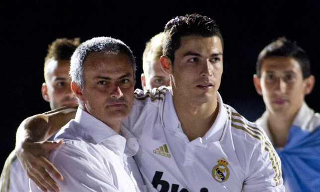 Real Madrid's Portuguese forward Cristiano Ronaldo (R) and Real Madrid's Portuguese coach Jose Mourinho celebrate winning Spanish League title on May 13, 2012 at the Santiago Bernabeu stadium in Madrid. The Santiago Bernabeu was given the first chance to celebrate Real Madrid's Portuguese coach Jose Mourinho's first Spanish title with 'los blancos' and resonated with a celebratory atmosphere to see skipper Iker Casillas lift the trophy after the match. AFP PHOTO/ Jaime REINA (Photo credit should read JAIME REINA/AFP/GettyImages)