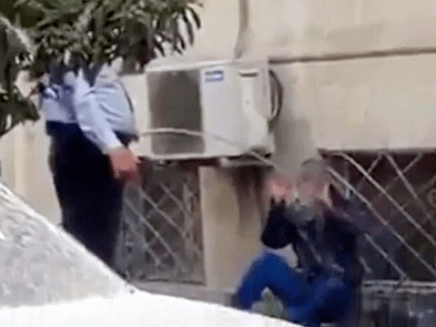 Police officer wakes man sleeping on street by spraying him with water