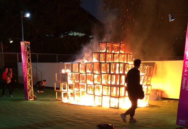 People look at a burning wooden jungle gym displayed at a Tokyo art festival in Tokyo on November 6, 2016. A five-year old boy who played inside the jungle gym was killed and two people were injured in the accident. / AFP PHOTO / JIJI PRESS / STR / Japan OUTSTR/AFP/Getty Images
