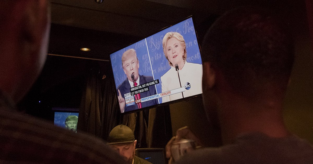 People watch as Donald Trump, 2016 Republican presidential nominee, and Hillary Clinton, 2016 Democratic presidential nominee, are seen on a television screen during a viewing party for the third U.S. presidential debate in San Francisco, California, U.S., on Wednesday, Oct. 19, 2016. Donald Trump is trying another wild-card play in the third and final presidential debate with Hillary Clinton in perhaps his last chance to reverse his campaign's spiral and halt his Democratic rival's rising electoral strength. Photographer: David Paul Morris/Bloomberg via Getty Images