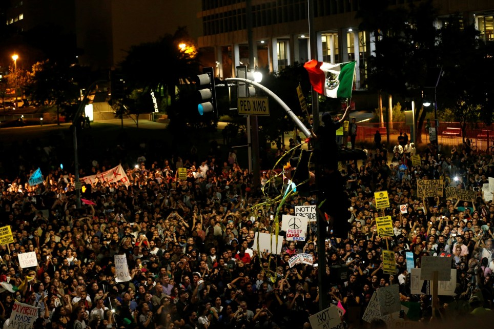 A protester waves a Mexican flag as others gather to protest to the election of Republican Donald Trump as the president of the United States outside City Hall in Los Angeles, California U.S., November 9, 2016. REUTERS/Mario Anzuoni TEMPLATE OUT