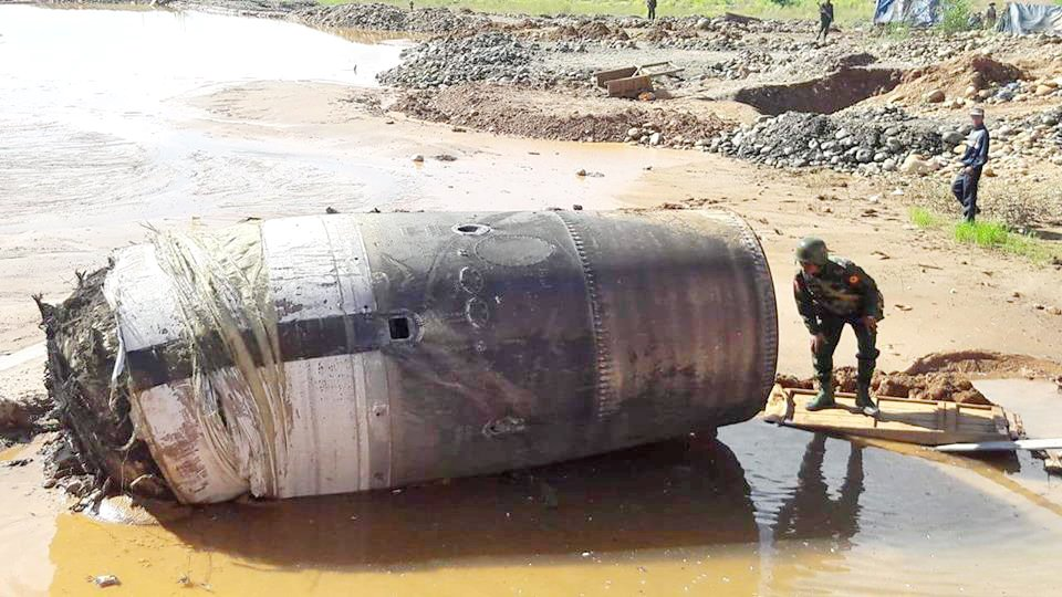 A soldier stands next to an object that fell from the sky in Hpakant township, Kachin State. Photo: Supplied / Ko Muang Myo Lone Khin villager Ko Maung Myo told The Myanmar Times yesterday that at 6am he heard what sounded like an explosion and felt the ground vibrate. Taken from http://www.mmtimes.com/index.php/national-news/mandalay-upper-myanmar/23626-unidentified-falling-object-in-hpakant.html check with legal before using