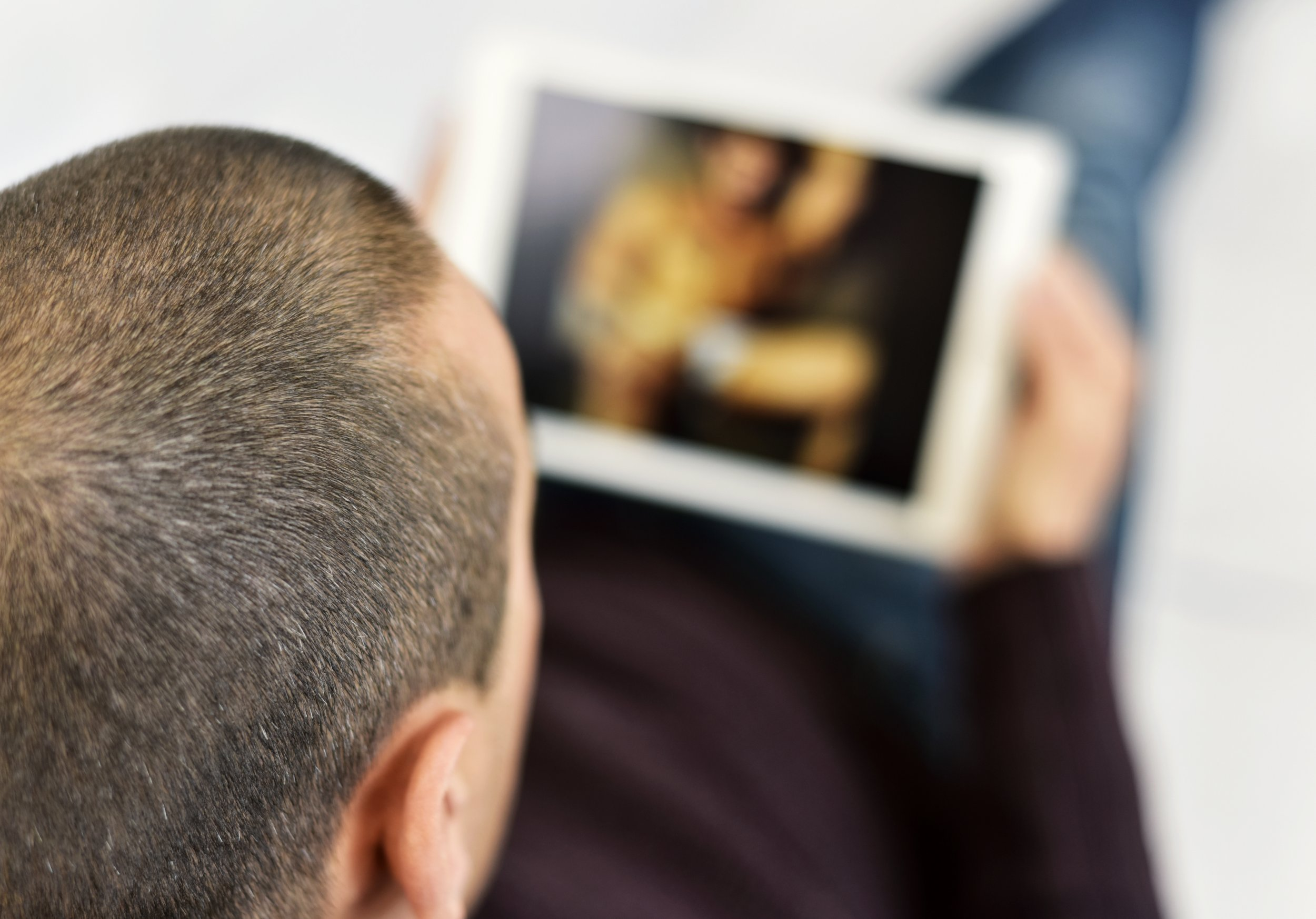 a young caucasian man lying on the couch watches porn in his tablet computer; Shutterstock ID 429846664