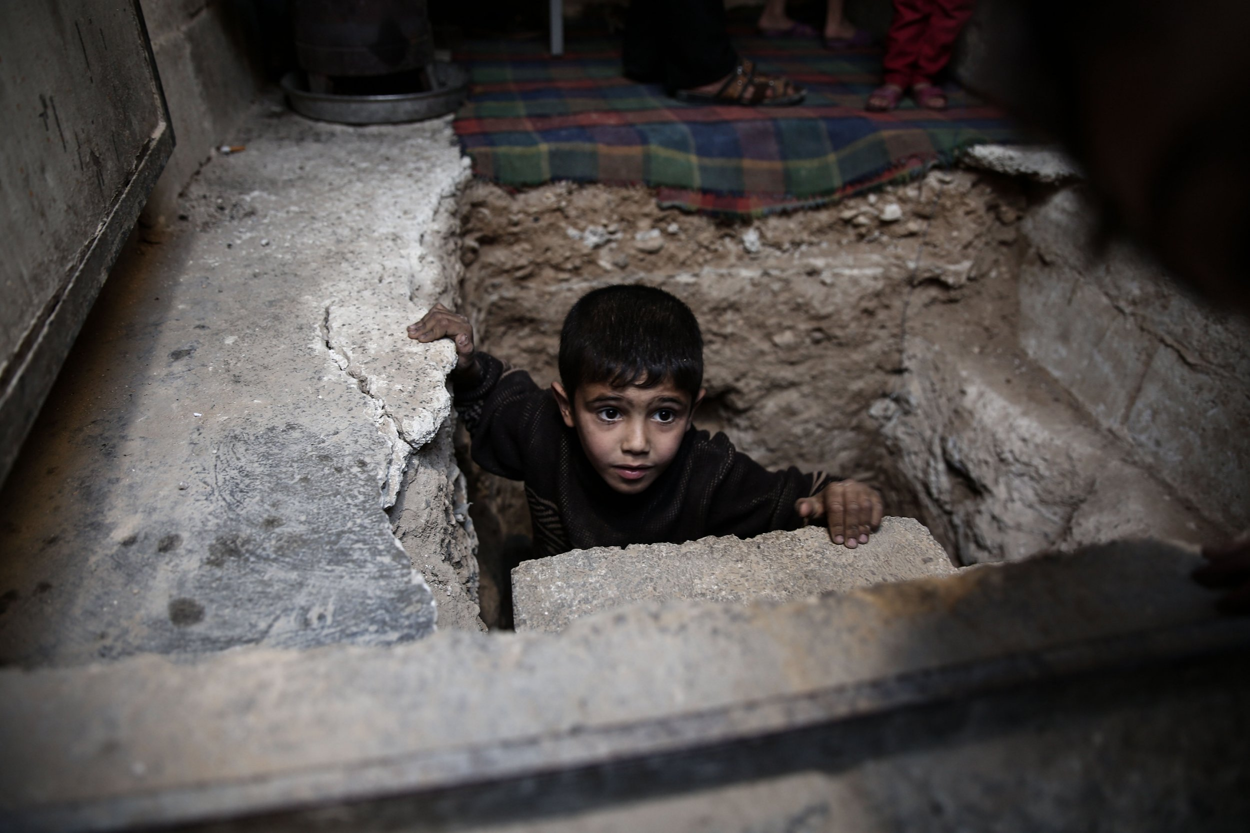 TOPSHOT - A Syrian boy climbs out of Abu Omar's shelter in the rebel-held town of Douma, on the eastern outskirts of Damascus, on October 30, 2016. Abu Omar, with the help of his neighbour, was able to dig and prepare an underground shelter consisting of a single room in the space of 2 weeks. The shelter is 4 meters below ground and has an air vent for emergencies. / AFP / Sameer Al-Doumy (Photo credit should read SAMEER AL-DOUMY/AFP/Getty Images)