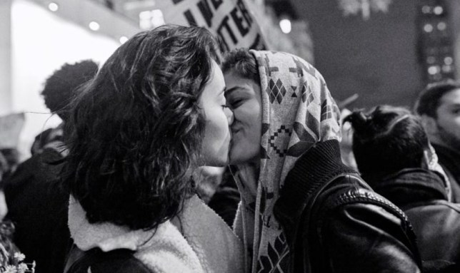 two women kiss at an anti-trump protest
