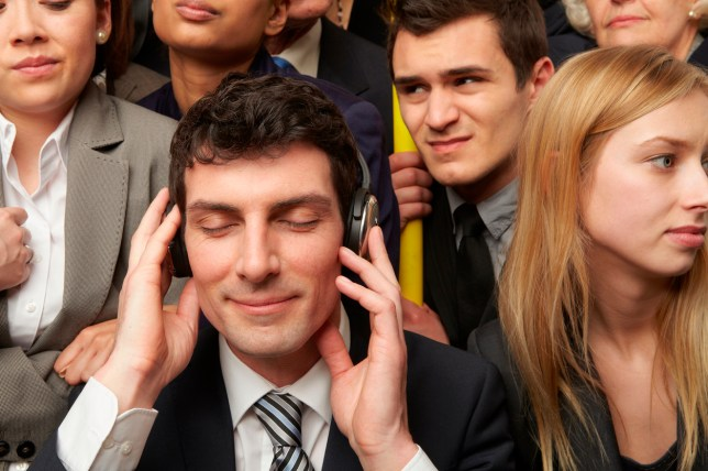 Businesswoman wearing headphones on subway train