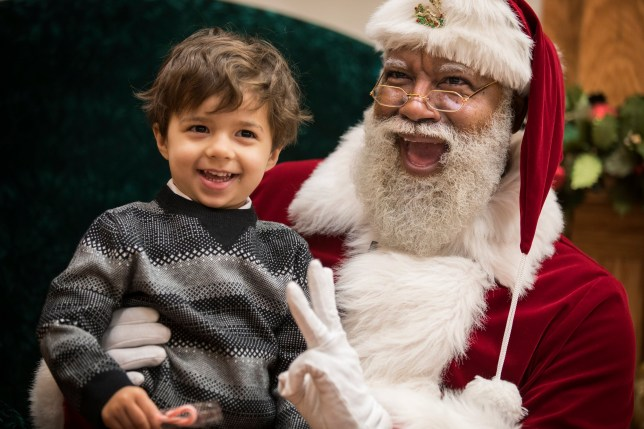 In this Thursday, Dec. 1, 2016 photo, Larry Jefferson, playing the role of Santa, smiles with Jack Kivel, of Prior Lake, for photos at the Santa Experience at Mall of America, in Bloomington, Minn. The nation's largest mall is hosting its first-ever black Santa Claus this this weekend. (Leila Navidi/Star Tribune via AP)